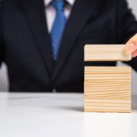 hands-businessman-stacking-wooden-blocks-table-business-concept_127345-189